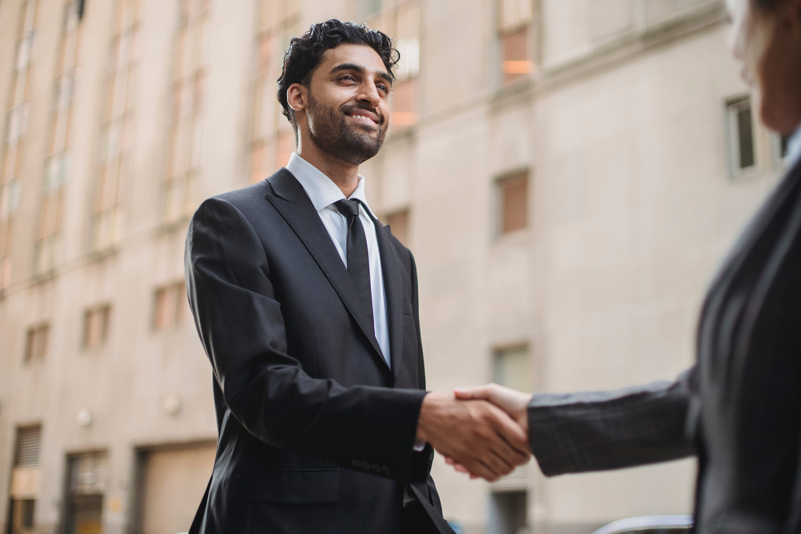 Business man in a suit shaking the hand of a colleague